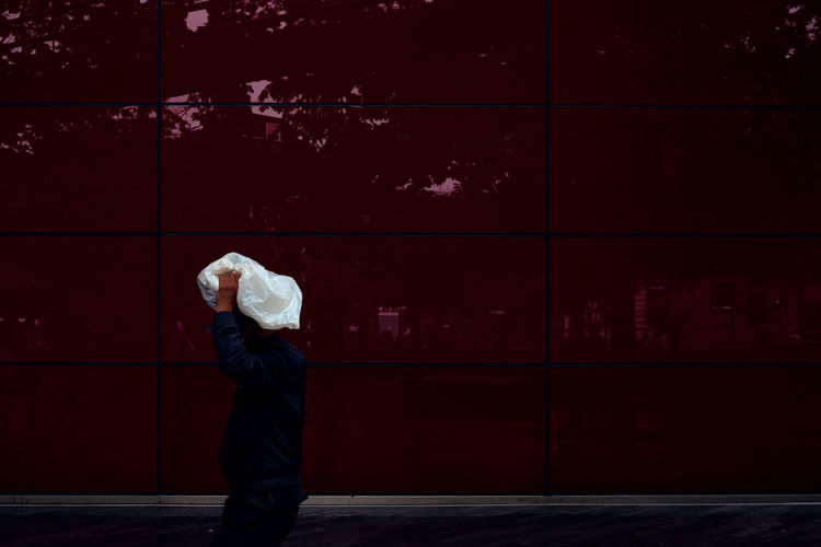 Side view of a woman standing against red wall