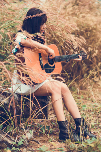 Woman playing guitar on field
