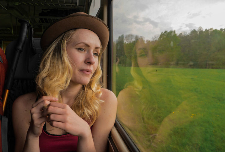 young caucasian woman traveling with train, looking out of a window on a open landscape Nature Transportation Travel Traveling View Woman Adventure Beautiful Woman Blond Hair Caucasian Female Front View Girl Hair Hairstyle Headshot Land Vehicle Landscape Leisure Activity Lifestyles Looking Mode Of Transportation Motion Movement One Person Outdoors Portrait Public Transportation Rail Transportation Real People Teenager Train Train - Vehicle Transportation Transportation Building - Type Of Building Vehicle Interior Window Women Young Women