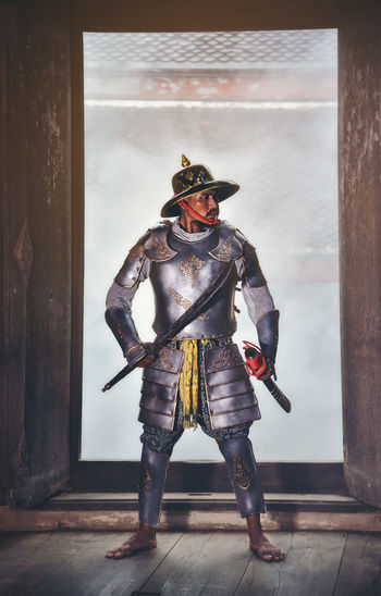 Man In Costume Holding Sword While Standing Against Window