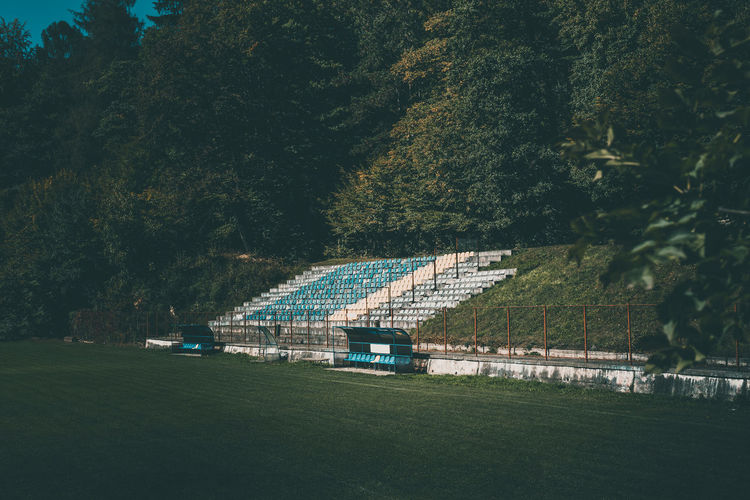 Soccer filed Bench Football Architecture Beauty In Nature Blue Built Structure Day Field Foliage Football Field Football Stadium Grass Green Color Nature No People Outdoors Plant Seat Seats Soccer Soccer Field Sport Stadium Sunlight Tree
