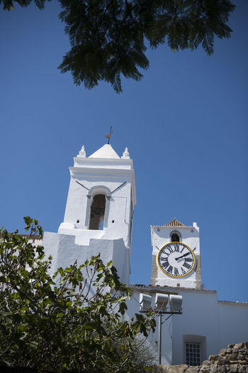 Low angle view of clock and bell tower of church against clear blue sky