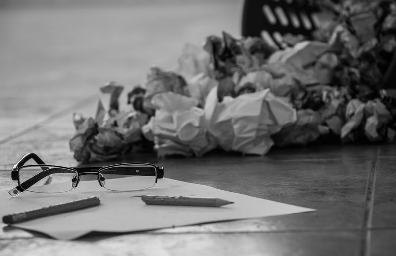 Close-up of crumpled paper with broken pencil and eyeglasses on table
