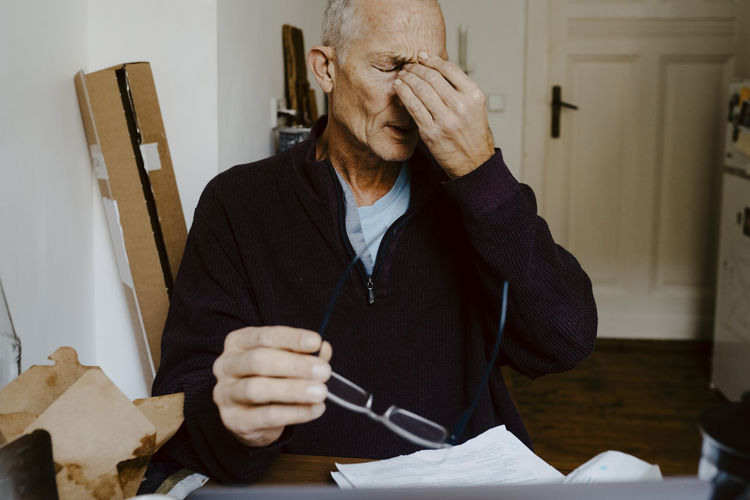 Midsection of man holding paper while sitting on table at home