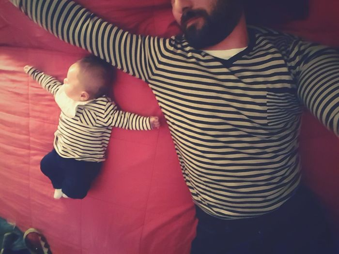 Portrait Of Man And Baby Lying On Bed