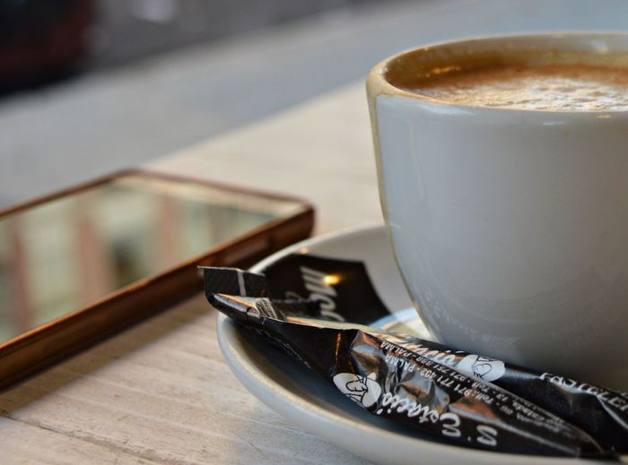 Relaxing Afternoon EyeEmNewHere Palma De Mallorca Relaxing Cafe Cafeteria Close-up Coffe Coffee Coffee - Drink Coffee Cup Crockery Cup Drink Focus On Foreground Food And Drink Freshness Hot Drink Indoors  Latte Mug No People Phone Refreshment Table