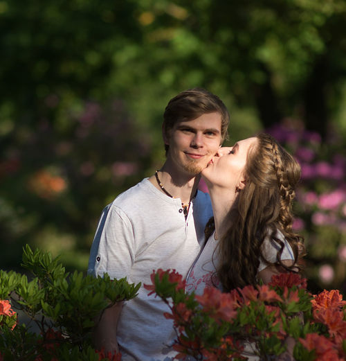 Woman kissing boyfriend standing amidst flowers at park