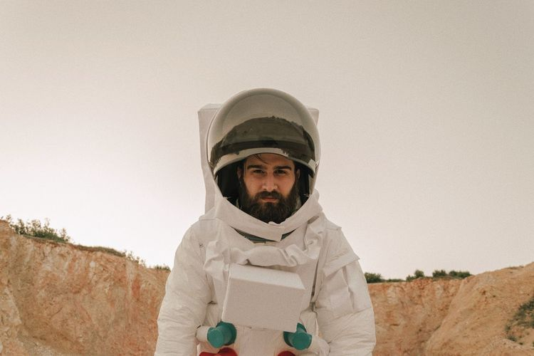 Portrait of man wearing space suit standing against sky