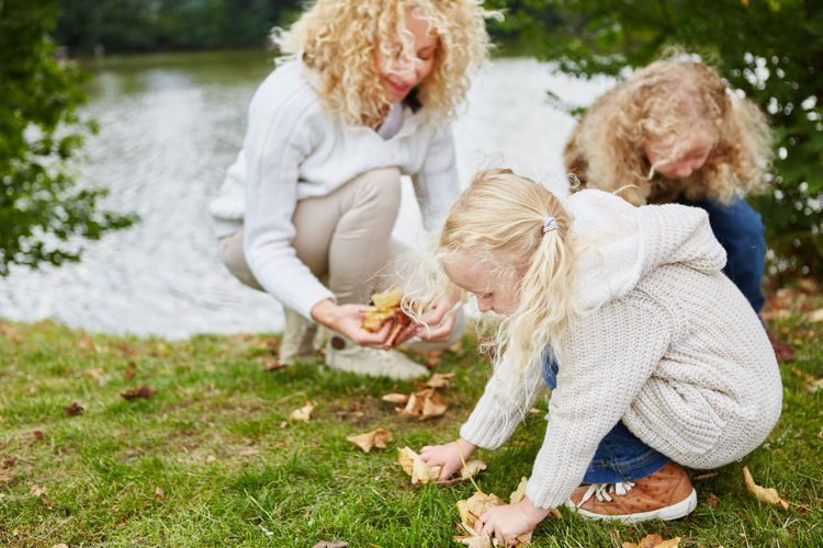 Mother and daughters collecting dried leaves from field at park