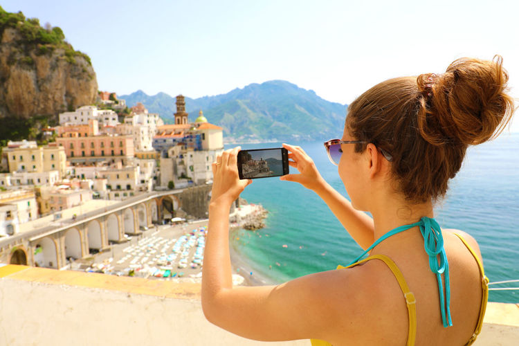 Woman photographing buildings from mobile phone by sea