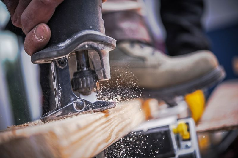 Close-Up Of Man Working On Plank