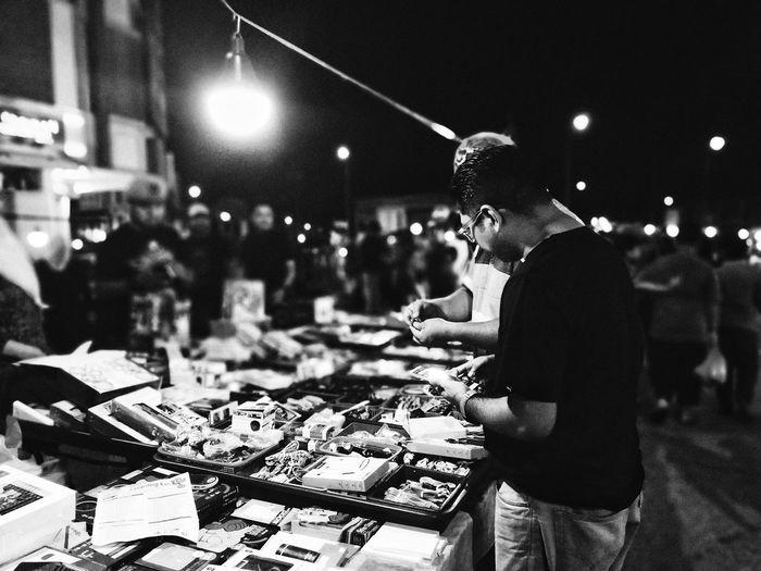 Men standing by illuminated market stall city at night