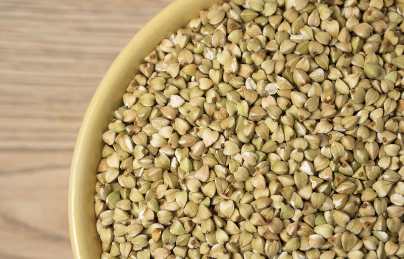 Natural fresh green buckwheat in ceramic bowl on wooden background. Top view. Natural; Agriculture; Diet; Food; Raw; Vegetarian; Fresh; Ingredient; Grain; Uncooked; Background; Healthy; Cereal; Green; Texture; Macro; Crop; Buckwheat; Nutrition; Meal; Dry; Organic; Cooking; Seed; White; Harvest; Plant; Vegan; Closeup; Cuisine; Unroa Food And Drink Food Wellbeing Healthy Eating Freshness Bowl Large Group Of Objects Indoors  Still Life Close-up Abundance Seed No People Raw Food Ingredient High Angle View Dried Food Container Directly Above Vegetarian Food Legume Family Cardamom