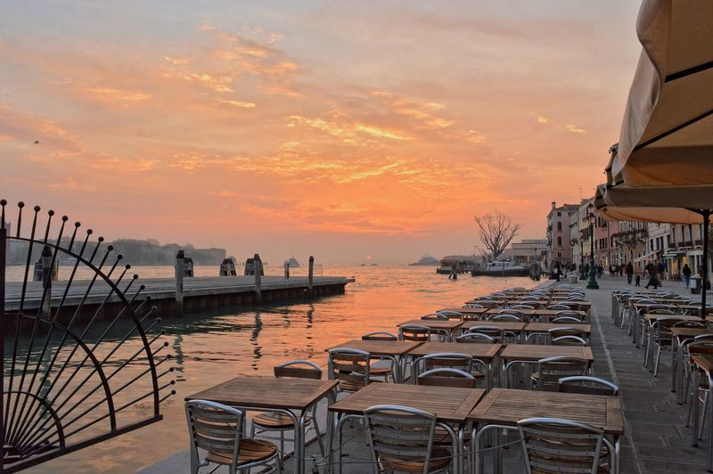 Tables and chairs at sidewalk cafe by sea during sunset