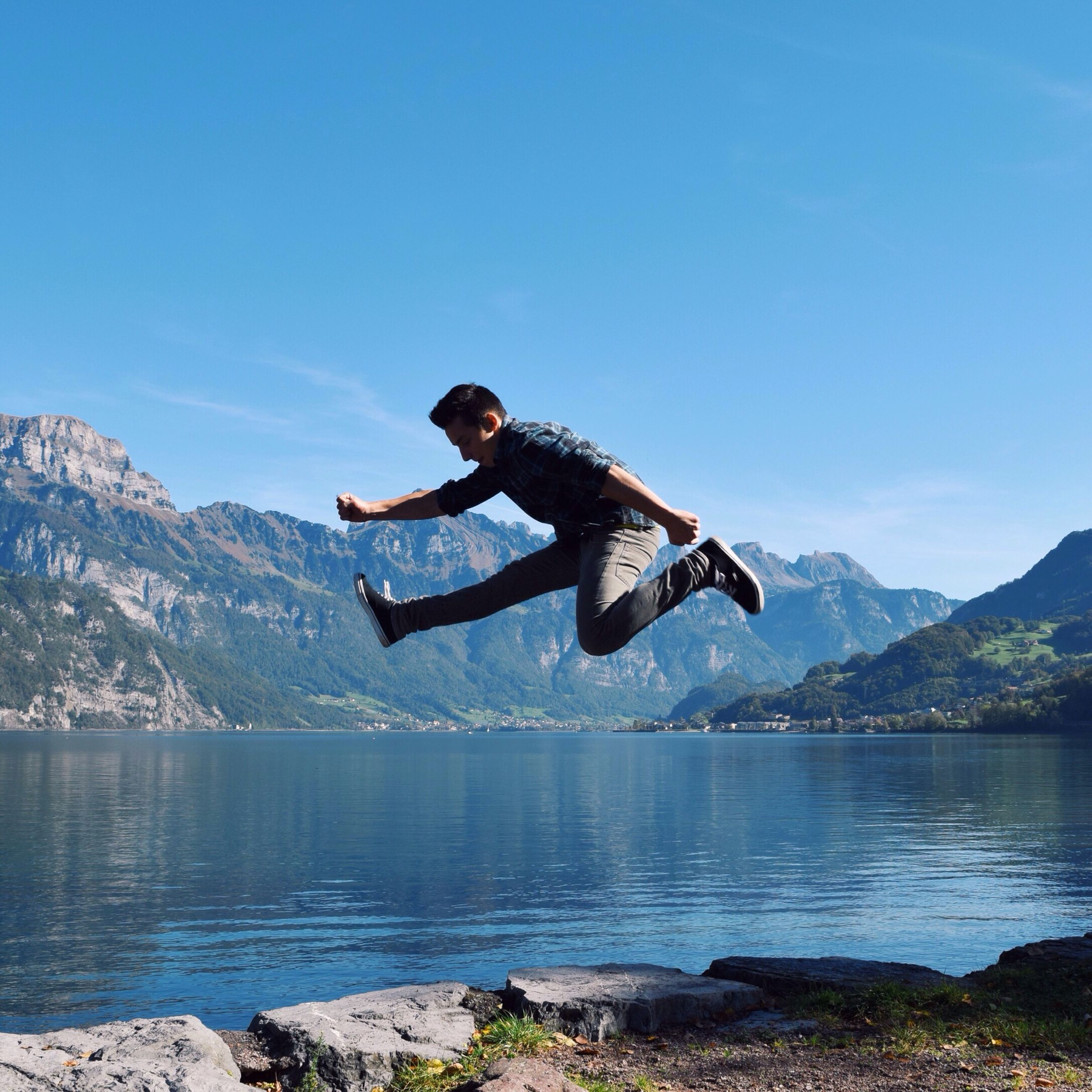 leisure activity, lifestyles, water, young adult, full length, mountain, lake, vacations, person, mountain range, enjoyment, casual clothing, blue, tranquil scene, clear sky, tranquility, scenics, nature
