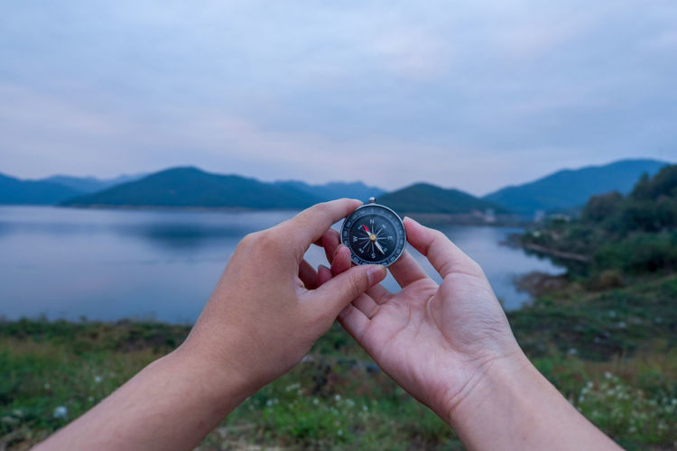 Cropped hands holding navigational compass against lake