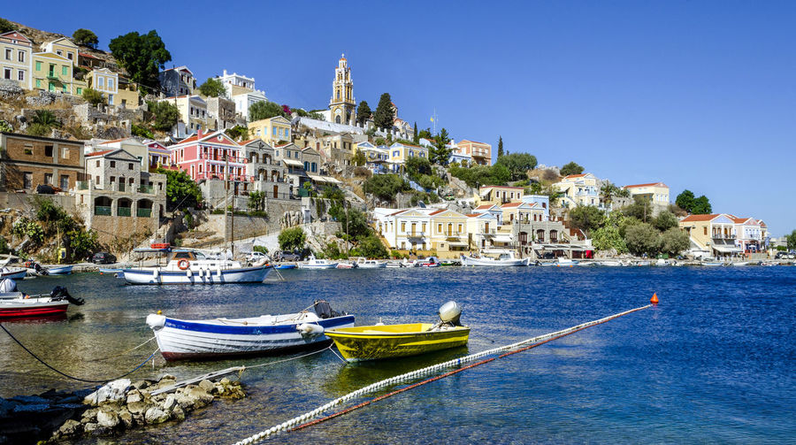 Boats moored in sea by townscape against clear blue sky