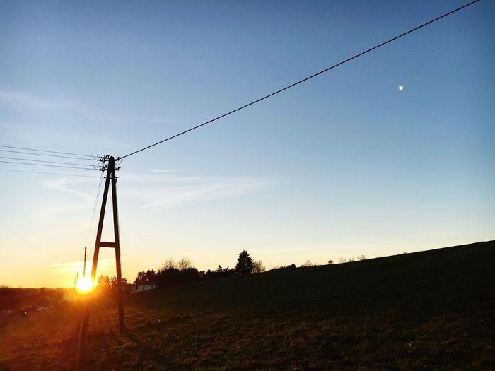 Telephone line on field against sky