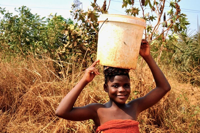 Portrait of smiling young woman carrying bucket on head in forest