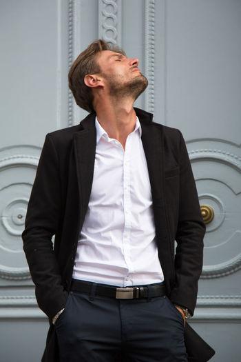 Handsome fashion model posing against closed door