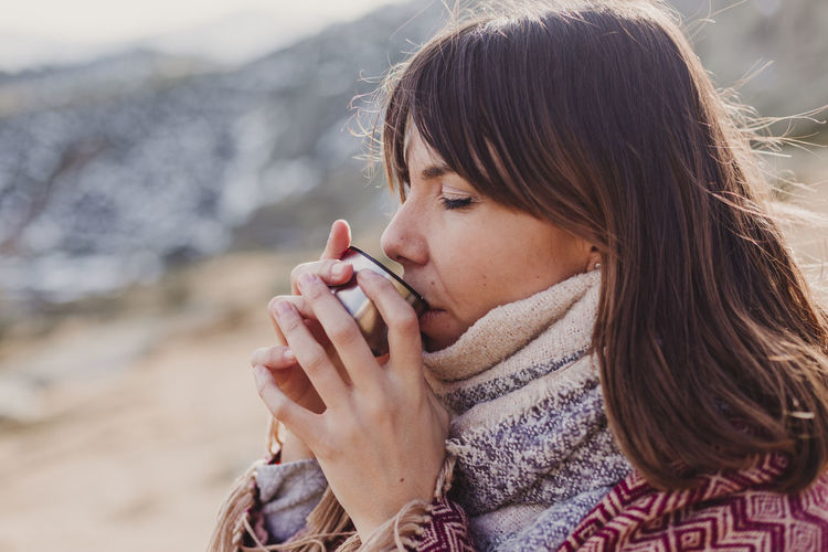 Close-up of woman drinking coffee in container during winter