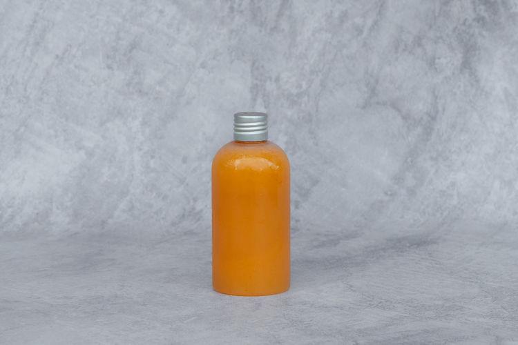Close-up of orange bottle against white background