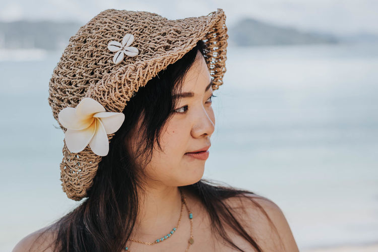 Close-up of woman wearing hat looking away against sea