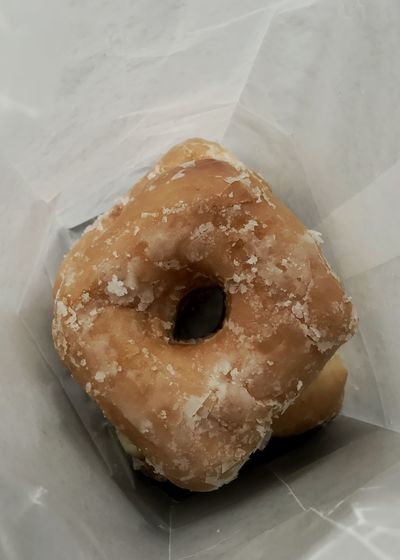 Glazed donut in a waxed bag. Donut Glazed Donut Glazed Yeast Donut Vertical Food Still Life High Angle View Freshness Sweet Food Ready-to-eat Indulgence Unhealthy Eating Close-up Waxed Bag Yeast Donut