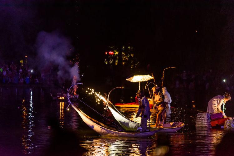 People enjoying in river at night