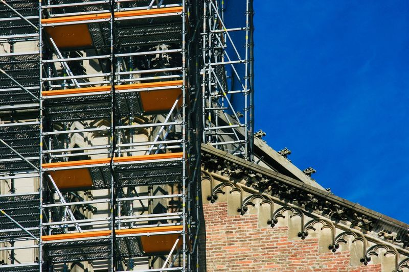 Construction Work Scaffolding Architecture Built Structure Low Angle View Building Exterior Sky Building No People Day Blue Outdoors Sunlight City The Past Pattern Metal Clear Sky History