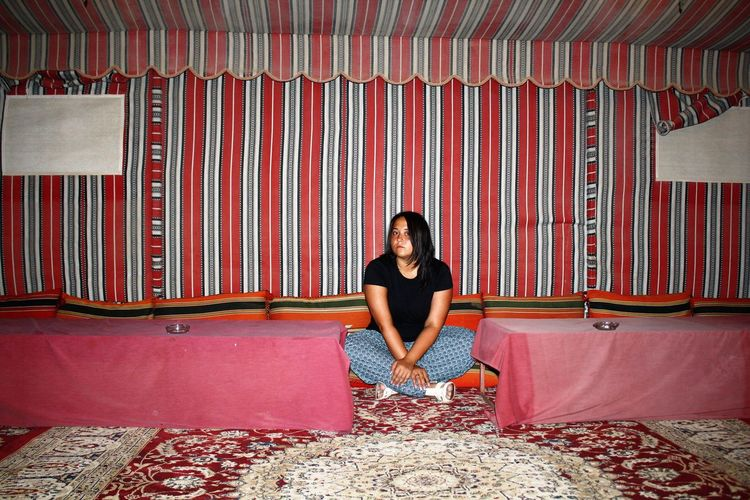 Portrait of young woman sitting on carpet
