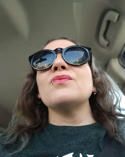 Woman wearing sunglasses while sitting in car