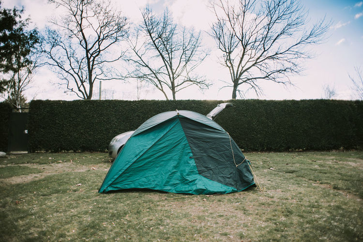 Tent on field against bare trees