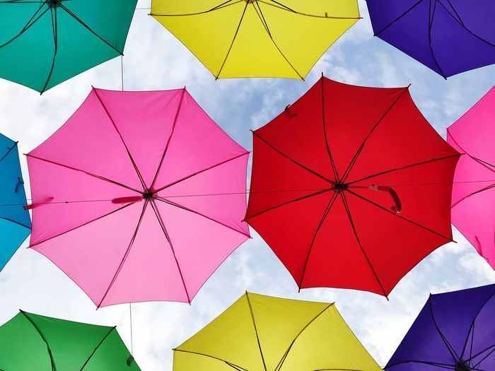 Low angle view of colorful umbrellas hanging against sky