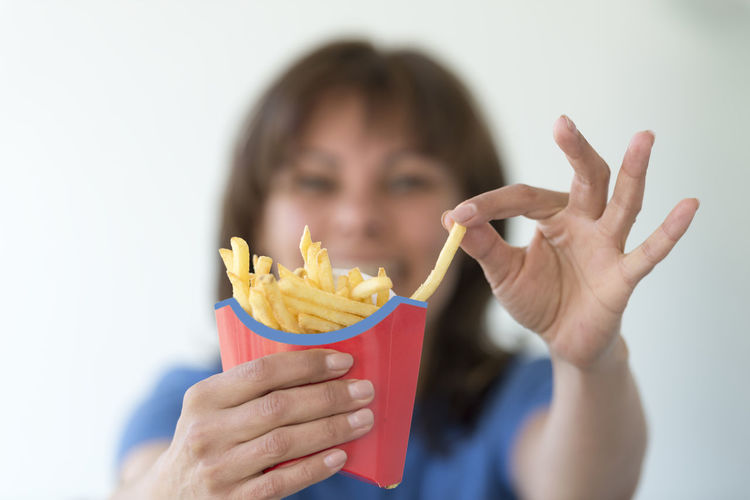 Woman eating french fries Adult Adults Only Box Close-up Day Delicate Eating Fast Food Focus On Foreground Food Food And Drink French Fries Head And Shoulders Headshot Holding Up Human Body Part Human Hand One Person One Young Woman Only People Positive Emotion Showing Smiling Unhealthy Eating Young Adult