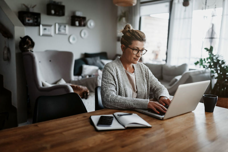 Woman using laptop on table while sitting at home