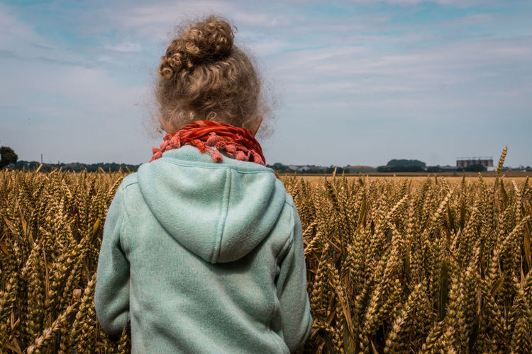 Rear View Of Girl Standing In Wheat Field Against Sky