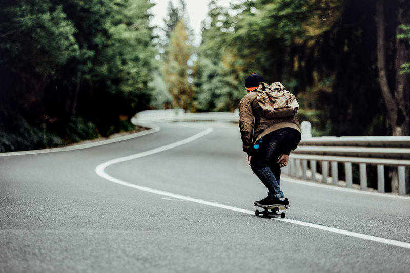 Rear View Of Man Skateboarding On Road