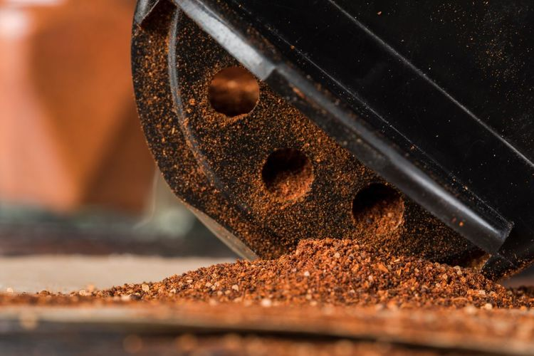 Close-up of red chili powder by grinding machine