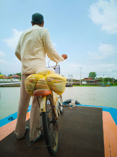 Rear view of man on bicycle against river