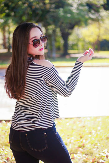 Portrait of beautiful woman wearing sunglasses standing at park