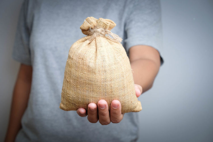 Midsection Of Man Holding Jute Sack