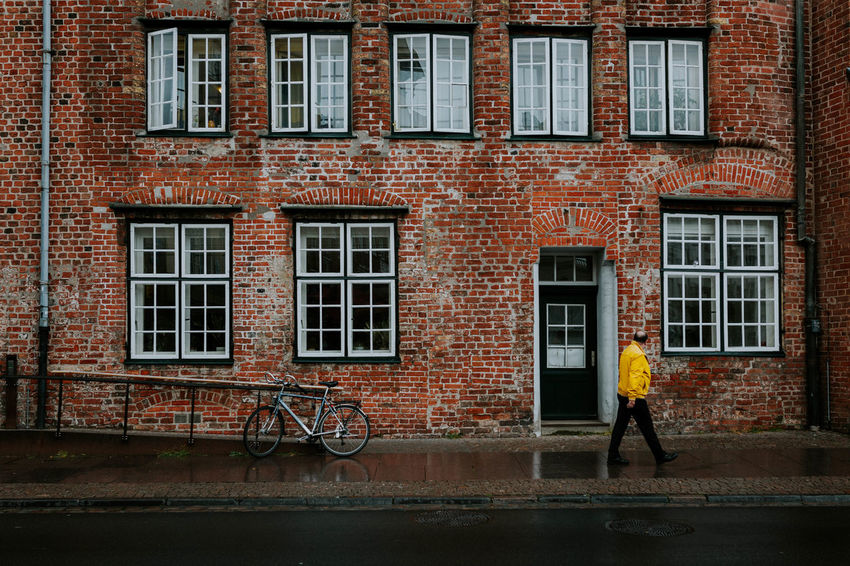 Brick Wall Adult Adults Only Architecture Bicycle Brick Building Brick House Brick Wall Building Exterior Built Structure City Day Full Length House Lifestyles Men One Man Only One Person Only Men Outdoors People Real People Standing Walking Window