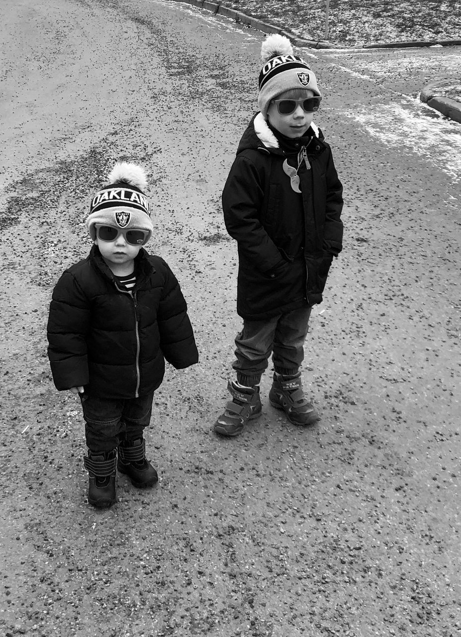 childhood, males, child, boys, men, two people, winter, full length, real people, front view, togetherness, females, standing, day, people, warm clothing, clothing, sibling, innocence, sister, outdoors