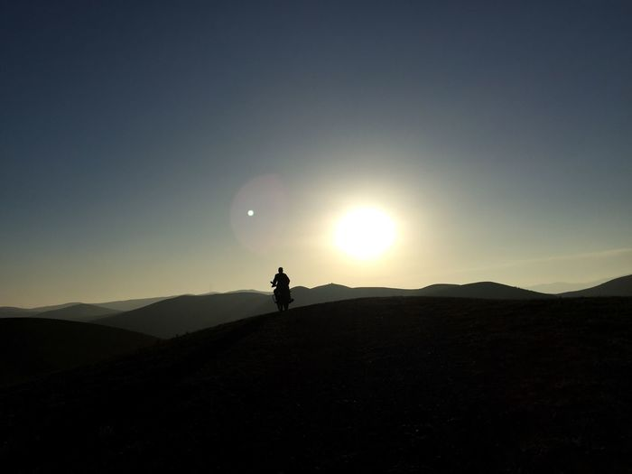 Silhouette Man Riding Motorcycle On Mountain Against Sky During Sunrise