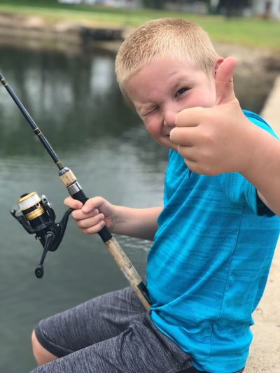 Portrait of cute boy showing thumbs up while fishing in lake
