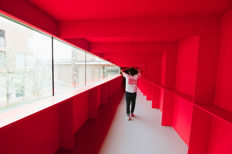 Red Dimension Bright EyeEm Best Shots Lost Wanderlust Adult Architecture Bold Building Built Structure Casual Clothing Day Full Length Indoors  Lifestyles One Person Real People Rear View Red Standing Window Women