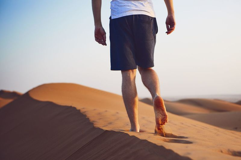 Low section of mid adult man walking on sand at desert against clear sky during sunset