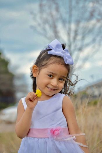 Portrait of smiling girl holding flower while standing on grassy field