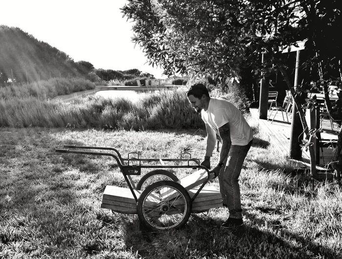 Side view of young man placing tiles on push cart at grassy field